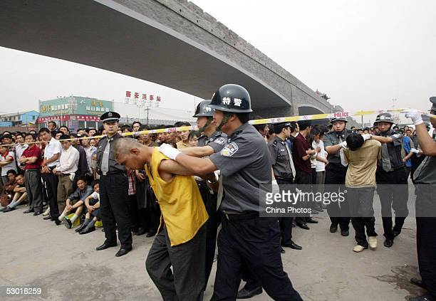Police parade criminals convicted of attacking policemen during a public sentence at a railway station on June 3 2005 in Xian of Shaanxi Province...