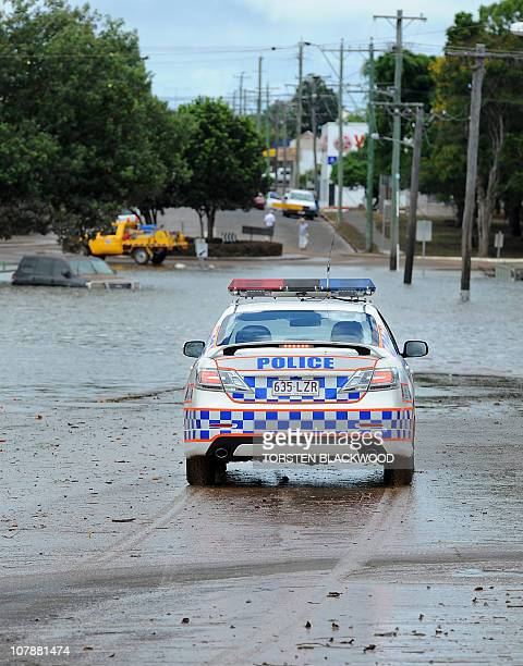 Police patrol a flooded street in the centre of Bundaberg as flood waters begin to recede on January 1 2011 Floods triggered by tropical cyclone...