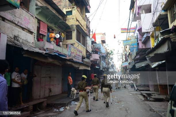 TOPSHOT Police patrol along a street as people gather to clap and make noise with kitchenware to thank essential service providers during a oneday...