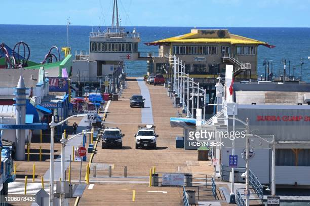 Police patrol an empty Santa Monica Pier in Santa Monica, California on March 23 as people are encouraged to stay at home to halt the spread of the...