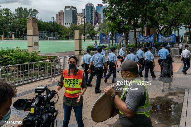 Police patrol as members of the press film at Victoria Park, after closing a venue where Hong Kong people traditionally gather annually to mourn the...