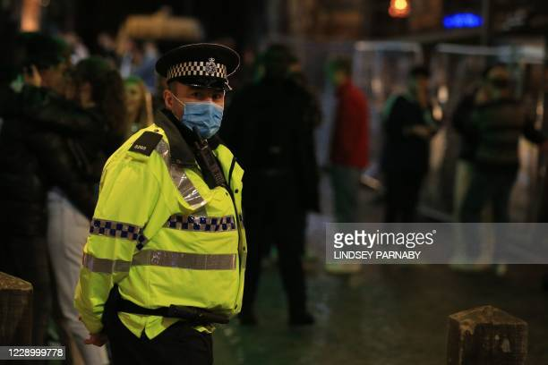 Police patrol as revellers enjoy a night out in the centre of Liverpool, north west England on October 10, 2020 ahead of new measures set to be...