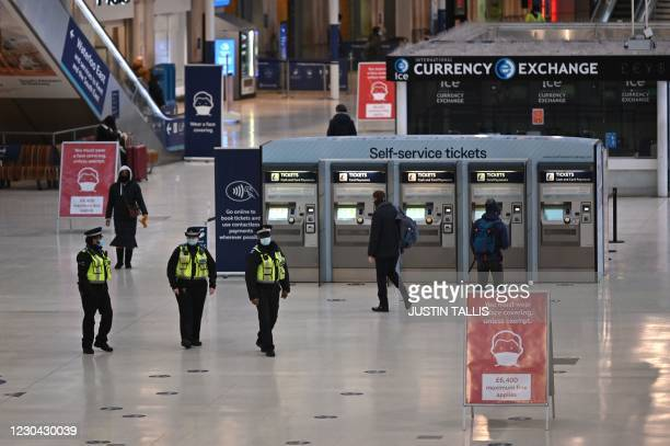 Police patrol at Waterloo station during the morning rush hour as Britain enters a national lockdown in London on January 5, 2021. - Britain entered...