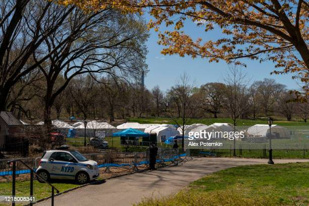 police patrol car guarding in front of the emergency field hospital opened in manhattan central park in response to the covid-19 pandemic. - field hospital stock pictures, royalty-free photos & images