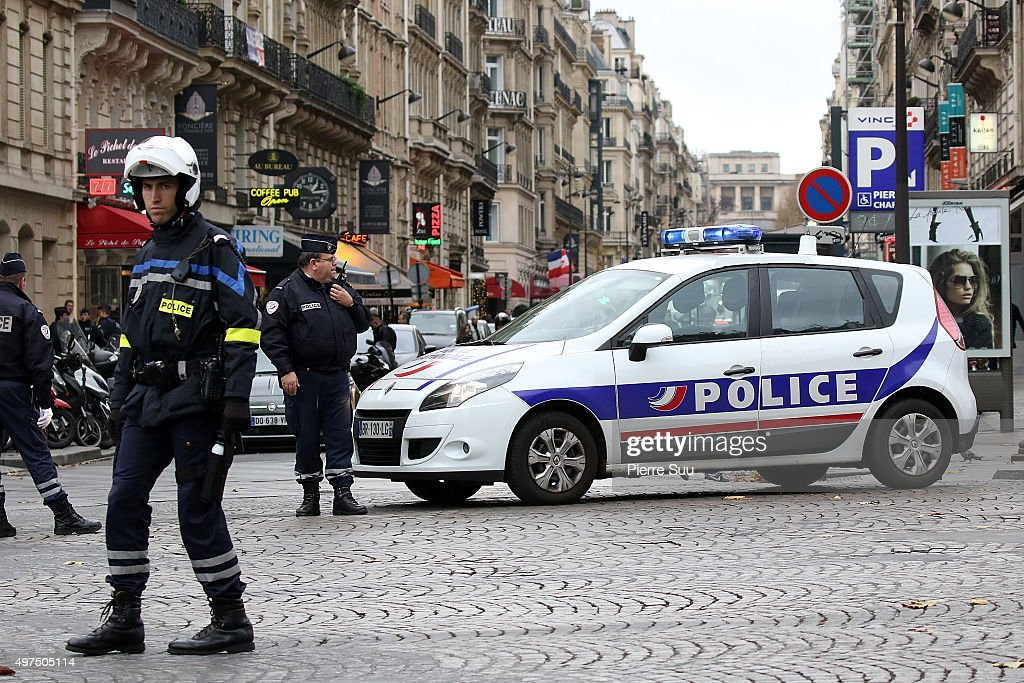 Police patrol cars and policemen are seen on the Champs Elysees on November 17, 2015 in Paris, France. Paris remains under heightened security following terrorist attacks , which left at least 129 people dead and hundreds more injured.
