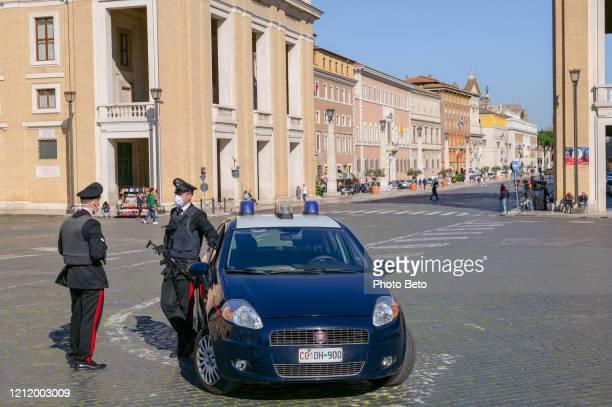eine italienische polizeistreife mit medizinischer maske kontrolliert den zugang zum platz des petersdoms - abstand halten stock-fotos und bilder