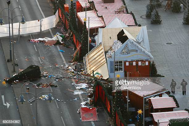 Police patrol inside the Christmas market area and past the destroyed booths two days after an attack with a truck in front of the...