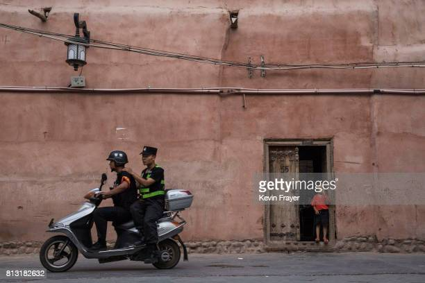 Police patrol on a scooter as an ethnic Uyghur boy stands in his doorway on June 27 2017 in the old town of Kashgar in the far western Xinjiang...