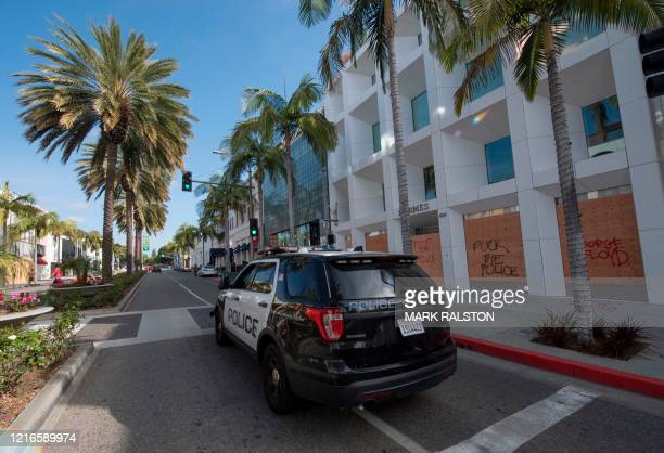 Police patrol past boarded up stores on the iconic Rodeo Drive, after demonstrators protested the death of George Floyd in Beverly Hills, California...