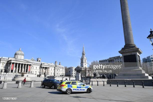 A police patrol stops in Trafalgar Square in central London on March 24 2020 after Britain ordered a lockdown to slow the spread of the novel...