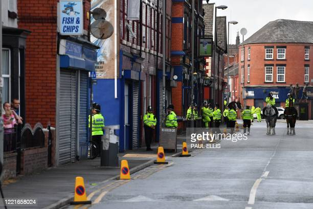 Police patrol the streets outside the ground ahead of the English Premier League football match between Everton and Liverpool at Goodison Park in...