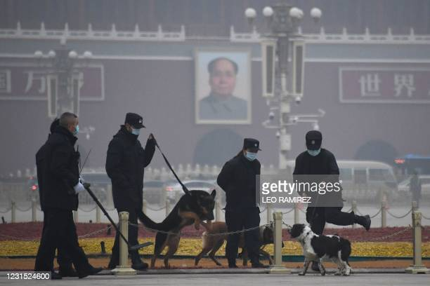 Police patrol with dogs in Tiananmen Square near the portrait of late communist leader Mao Zedong on Tiananmen Gate, ahead of the opening session of...