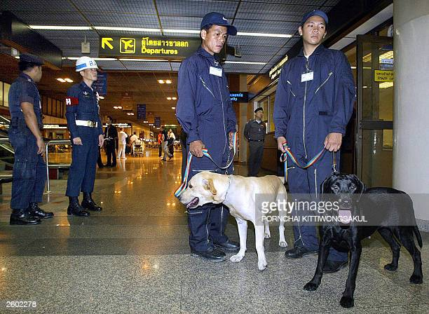 Police patrol with their dogs inside Bangkok's international airport 16 October 2003 as security is beefed up ahead of the APEC summit Thailand has...