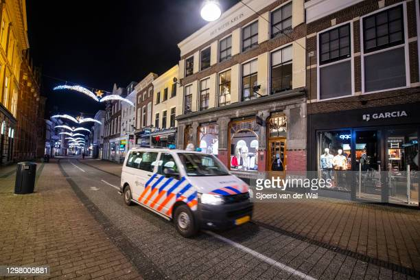 Police patrolling a deserted street in the city center of Zwolle during the start of the evening curfew after the Dutch government announced new...