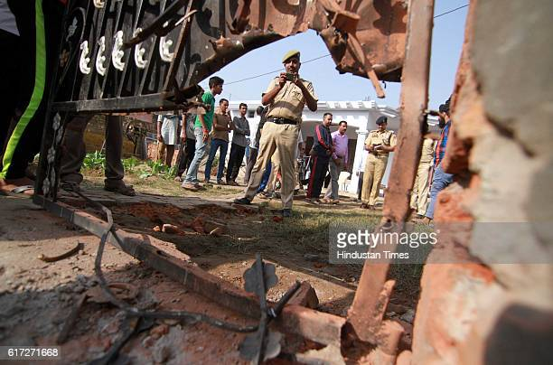 A police personal takes picture in his mobile of damaged gate of the house in Vidipur Jatta village at yesterday night in RS Pura sector about 45 km...
