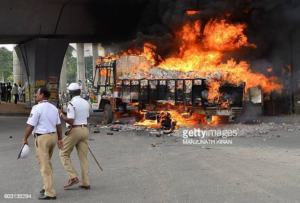 Police personel walk past a burning truck from neighbouring state Tamil Nadu after it was set alight by agitated proKarnataka activists as the...