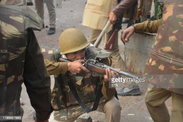 Police personnel aims his gun towards protesters during demonstrations against India's new citizenship law in Meerut on December 20, 2019. - Five...