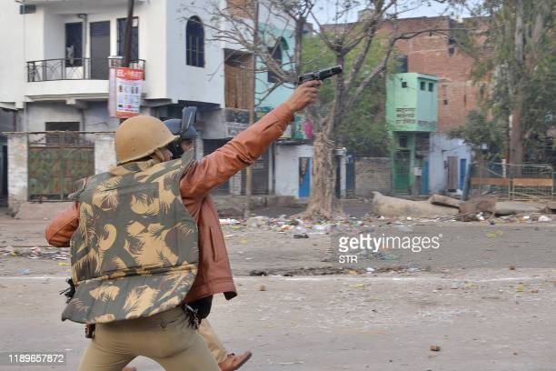 A police personnel aims his gun towards protesters during demonstrations against India's new citizenship law in in Kanpur on December 20 2019 Five...