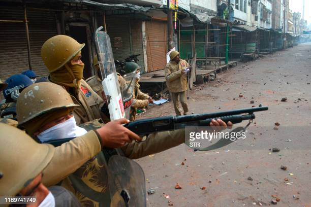 A police personnel aims his gun towards protesters during demonstrations against India's new citizenship law in Kanpur on December 21 2019 Thousands...