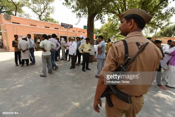 Police personnel and villagers at Kotwali Jewar on May 25 2017 in Greater Noida India A gang of highway robbers allegedly dragged and raped four...