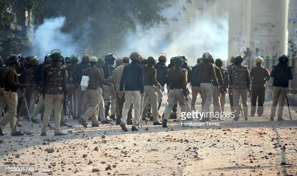 Police personnel are seen at work during violent clashes between anti and pro CAA demonstrations, at Jaffarabad, near Maujpur on February 24, 2020 in...