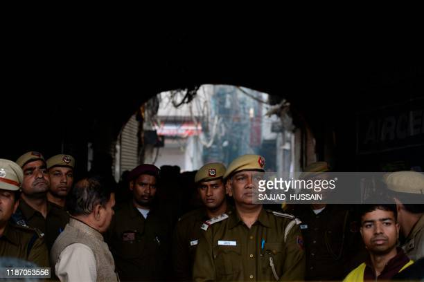 Police personnel block a street leading to a factory site where a fire broke out in Anaj Mandi area of New Delhi on December 8 2019 At least 43...