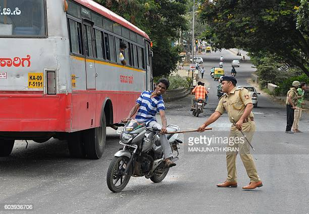 TOPSHOT A police personnel canes a motorcyclist during a curfew following violence in the city due to the Cauvery water sharing dispute with...