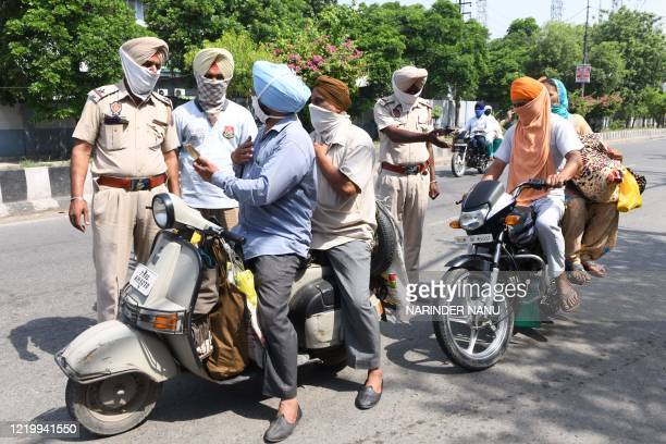 Police personnel check commuters after strict lockdown norms for weekends and public holidays were imposed as a preventive measure against the...