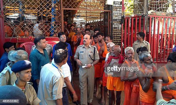 Police personnel conduct investigations at the site of a stampede by pilgrims at the Baidyanath Jyotirlinga temple complex in Deoghar district of...