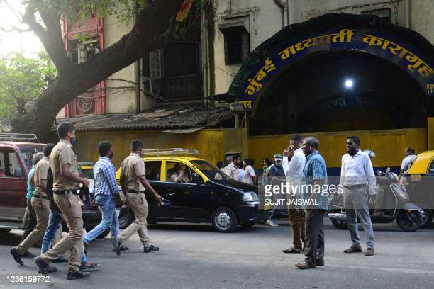 Police personnel cross a road near the entrance of the Arthur Road Jail, where Aryan Khan, son of Bollywood actor Shah Rukh Khan, is under custody...