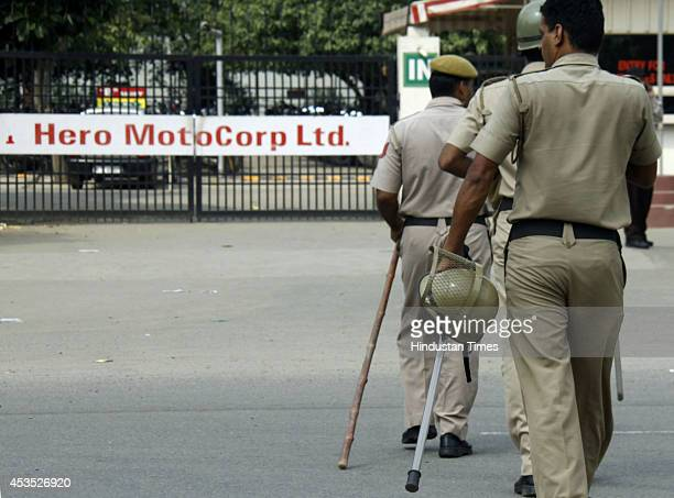 Police personnel deployed at the gate of Hero MotoCorp company as hundreds of employees protest outside on August 12 2014 in Gurgaon India The...