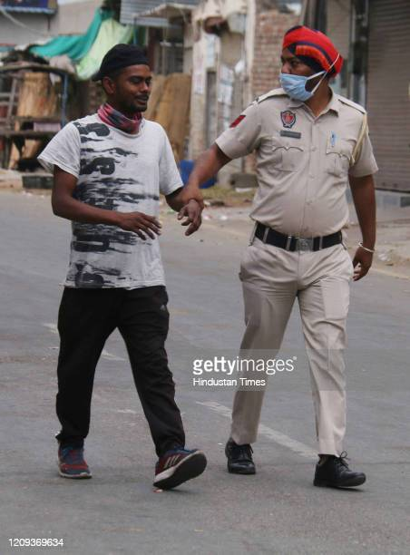 Police personnel detain a man found defying curfew, on day fourteen of the 21 day nationwide lockdown to check the spread of coronavirus, on April 7,...