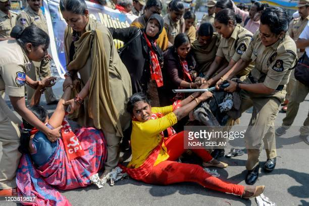 TOPSHOT Police personnel detain members of Communist Party of India as they demand the resignation of Union Home Minister Amit Shah for the...