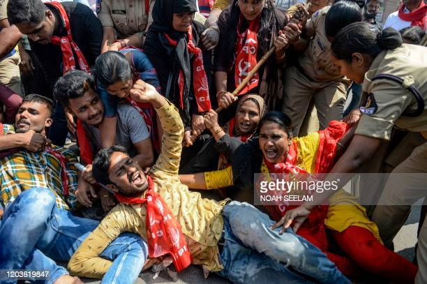 Police personnel detain members of Communist Party of India as they demand the resignation of Union Home Minister Amit Shah for the responsibility...