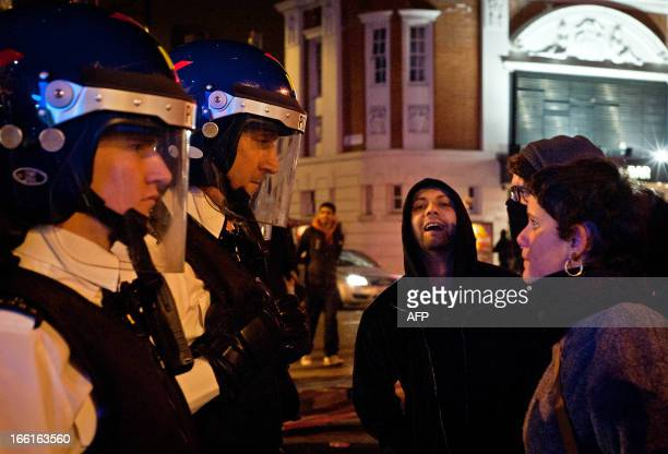 Police personnel dressed in riot helmets patrol the streets of Brixton in south London in the early hours of April 9 following a 'party' to celebrate...