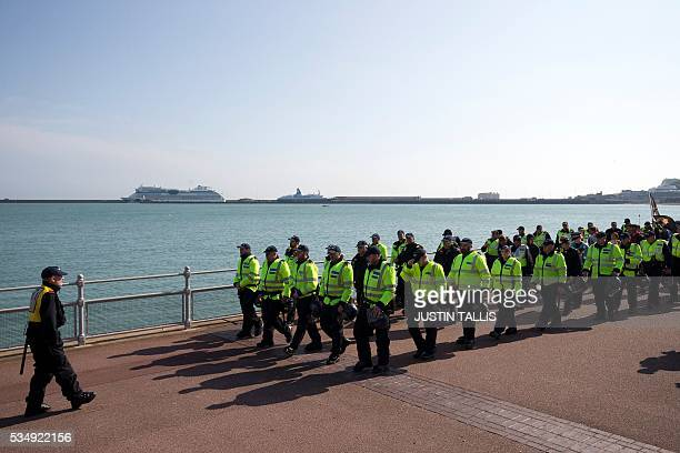 Police personnel escort a demonstration by far right protesters in the town of Dover in south east England on May 28 2016 / AFP / JUSTIN TALLIS