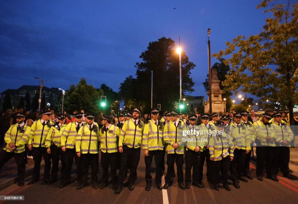 Police personnel form a cordon in front of protestors in Brixton, south London, during a demonstration against police brutality in the US, on July 9, 2016, after two recent incidents where black men have been shot and killed by police officers. / AFP / Daniel Leal-Olivas