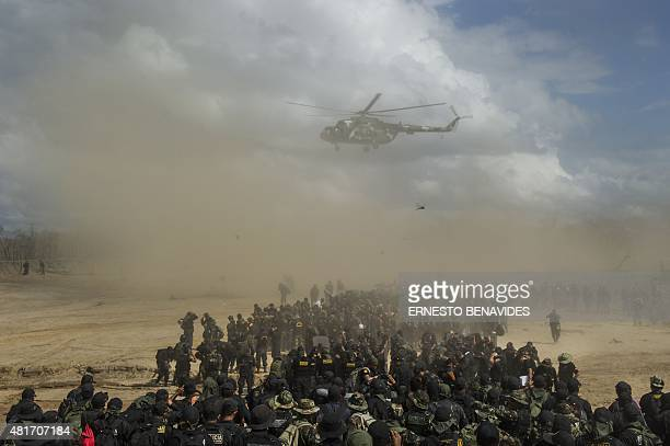 Police personnel gather on the landing zone as the helicopter arrives to pick them up at the end of an interdiction operation in the illegal gold...