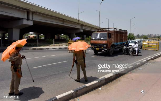 Police personnel holding umbrellas to protect from the rising summer temperatures as they screen vehicles at Ghaziabad border near Ghazipur during...