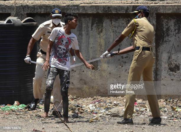 Police personnel in action against the people who outside their house during nationwide lockdown due to COVID 19 pandemic at Dharavi on April 11 2020...