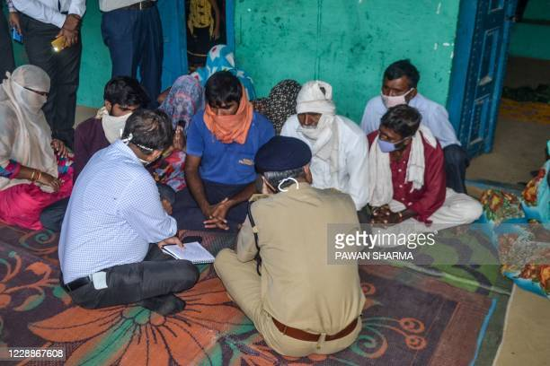 Police personnel interact with relatives of the 19-year-old woman allegedly gang-raped and killed by four men in Bool Garhi of Hathras district in...