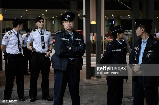 Police personnel keep vigil before Erwiana Sulistyaningsih an Indonesian maid allegedly tortured by her Hong Kong employer is escorted outside the...