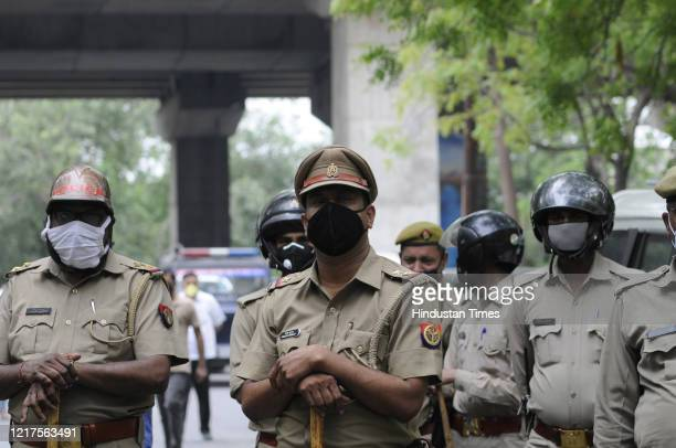 Police personnel look on as BJP party workers sit outside the Sector 24 police station in protest after a local leader was arrested for allegedly...