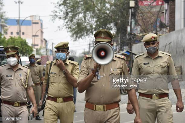 Police personnel make annopuncement at sector 8 road during curfew imposed to curb the spread of coronavirus disease on May 7, 2021 in Noida, India.