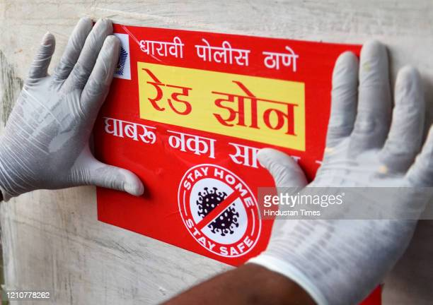 Police personnel pastes a red zone notice after MCGM declared the area a containment zone in Dharavi, during the nationwide lockdown against...