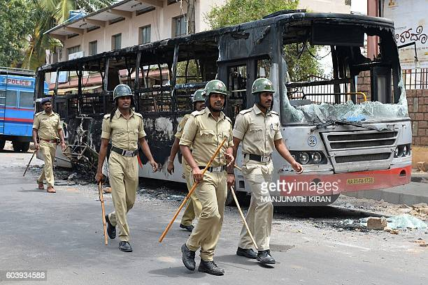 Police personnel patrol during a curfew following violence in the city due to the Cauvery water sharing dispute with neighbouring state Tamil Nadu in...
