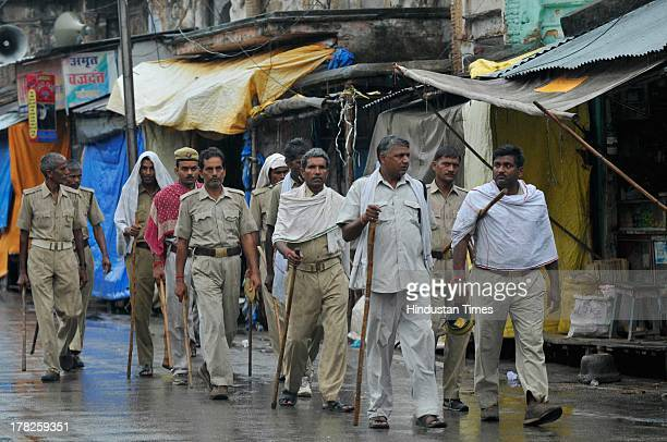 Police personnel patrols the streets during rainfall on August 27, 2013 in Ayodhya, India. Two days after the failed Parikarma attempt by Vishwa...