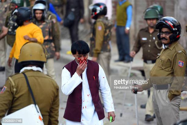 Police personnel rescue a man during violent clashes between anti and pro CAA demonstrations, at Jaffarabad, near Maujpur on February 24, 2020 in New...