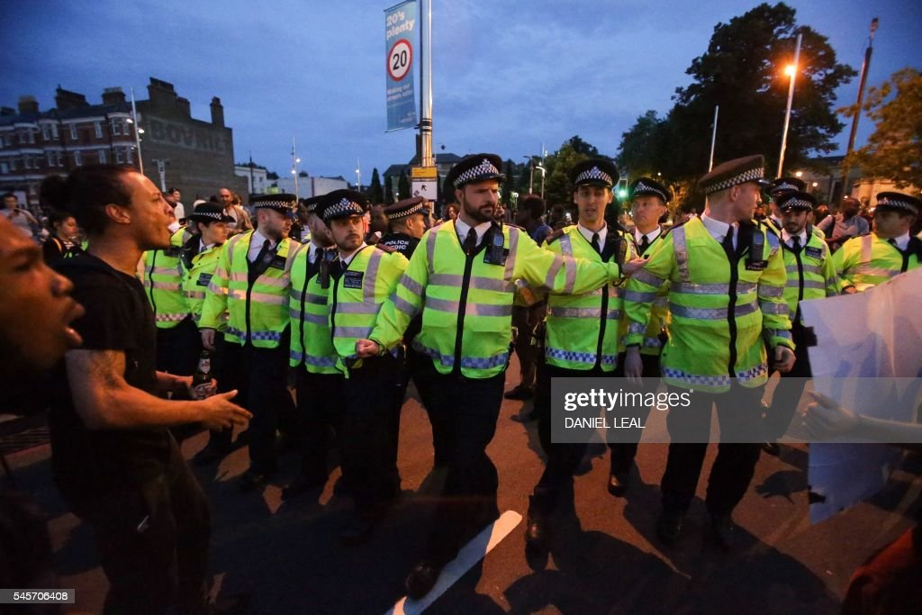 Police personnel retreat from protestors in Brixton, south London, during a demonstration against police brutality in the US, on July 9, 2016, after two recent incidents where black men have been shot and killed by police officers. / AFP / Daniel Leal-Olivas