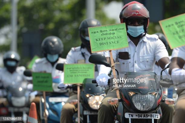 Police personnel riding on motorbikes hold placards during a Covid-19 coronavirus awareness rally in Chennai on April 29, 2021.